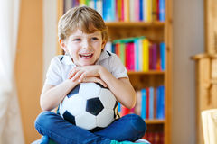 Kid boy watching soccer or football game on tv. Little blond preschool kid boy with ball watching soccer european cup game on tv. Funny child fan having fun and Stock Photos
