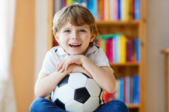 Kid boy watching soccer or football game on tv. Little blond preschool kid boy with ball watching soccer european cup game on tv. Funny child fan having fun and Stock Photo