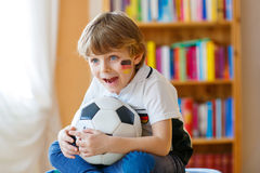 Kid boy watching soccer or football game on tv. Little blond preschool kid boy with ball watching soccer european cup game on tv. Funny child fan having fun and Stock Photography