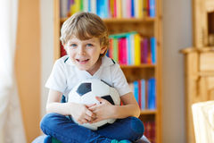 Kid boy watching soccer or football game on tv. Little blond preschool kid boy with ball watching soccer european cup game on tv. Funny child fan having fun and Royalty Free Stock Photos