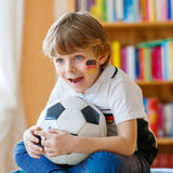 Kid boy watching soccer or football game on tv. Little blond preschool kid boy with ball watching soccer european cup game on tv. Funny child fan having fun and Stock Image