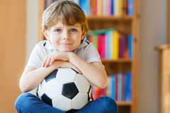 Kid boy watching soccer or football game on tv. Little blond preschool kid boy with ball watching soccer european cup game on tv. Funny child fan having fun and Royalty Free Stock Photo