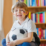 Kid boy watching soccer or football game on tv. Little blond preschool kid boy with ball watching soccer european cup game on tv. Funny child fan having fun and Royalty Free Stock Photography