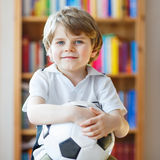 Kid boy watching soccer or football game on tv. Little blond preschool kid boy with ball watching soccer european cup game on tv. Funny child fan having fun and Royalty Free Stock Images