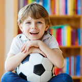 Kid boy watching soccer or football game on tv. Little blond preschool kid boy with ball watching soccer european cup game on tv. Funny child fan having fun and Royalty Free Stock Image