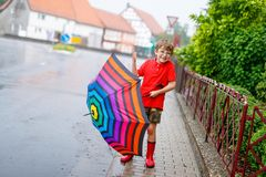 Kid boy wearing red rain boots and walking with umbrella. Kid boy wearing red rain boots and walking with colorful umbrella on city street. Child with glasses on Stock Photos