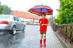 Kid boy wearing red rain boots and walking with umbrella. On city street. Child with glasses on summer day Stock Photos