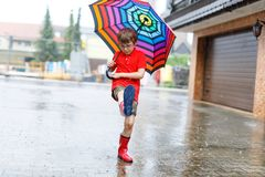 Kid boy wearing red rain boots and walking with umbrella. Kid boy wearing red rain boots and walking with colorful umbrella on city street. Child with glasses on Stock Photo