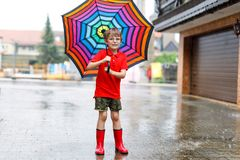 Kid boy wearing red rain boots and walking with umbrella. Kid boy wearing red rain boots and walking with colorful umbrella on city street. Child with glasses on Royalty Free Stock Photos