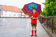 Kid boy wearing red rain boots and walking with umbrella. Kid boy wearing red rain boots and walking with colorful umbrella on city street. Child with glasses on Royalty Free Stock Photography