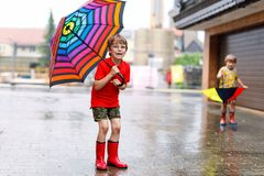 Kid boy wearing red rain boots and walking with umbrella. Kid boy wearing red rain boots and walking with colorful umbrella on city street. Child with glasses on Stock Images