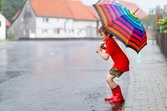 Kid boy wearing red rain boots and walking with umbrella. Kid boy wearing red rain boots and walking with colorful umbrella on city street. Child with glasses on Royalty Free Stock Image