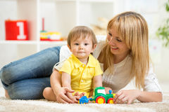 Kid boy and woman playing with toy indoor Stock Photos