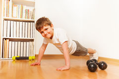 Kid boy working out on the floor, doing push-ups Stock Images