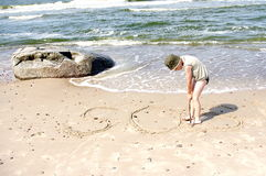 Kid boy writing SOS beach shore sea water. Little boy alone by the sea needs help so writing the help sign - SOS Royalty Free Stock Images