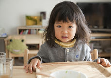 Kid breakfast. Young Asian Girl waiting for breakfast Royalty Free Stock Image