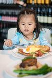Kid breakfast. Young Asian Girl waiting for breakfast stock photography