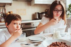 Kid brother and teen sister having breakfast at home in modern white kitchen and eating snacks Royalty Free Stock Image