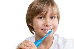 Kid brushing his teeth with toothbrush isolated on white backgroun. Smiling kid brushing his teeth with toothbrush isolated on white backgroun stock photo