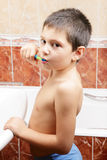 Kid brushing teeth in bathroom Royalty Free Stock Images