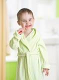 Kid brushing teeth in bathroom Stock Photo