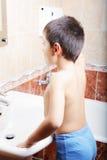 Kid brushing teeth looking to mirror Stock Photos