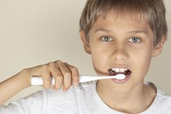 Kid brushing teeth with white electric toothbrush. Child brushing teeth with white electric toothbrush royalty free stock photo