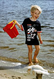 A kid with the bucket. A child walking at the shore of lake with red bucket Royalty Free Stock Photo