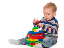 Kid building a toy house. A smiling little boy is building a toy house sitting on the floor; isolated on the white background Royalty Free Stock Image