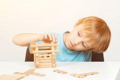 Kid builds small wooden house. Eco house. Construction concept. Little boy plays with blocks. Childhood and development. Cute kid. Playing at home. Smart boy stock photography