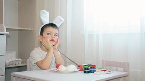 A boy dressed as a hare does not know what color to decorate the color of the Easter egg. The kid in the Bunny suit doesn`t know what color to paint the egg stock footage