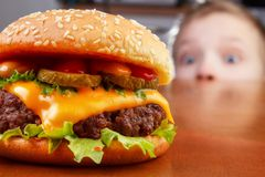 Kid and burger. Hungry young boy is staring and smelling a burger Stock Photo
