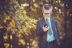 Kid businessman with laptop on the park background Royalty Free Stock Image