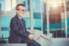 Kid businessman with laptop Stock Images