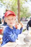 Kid at cafe. Cheerful happy boy sitting in outdoor cafe and enjoying cookie and hot chocolate, urban lifestyle concept Royalty Free Stock Images