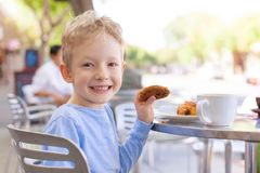 Kid in cafe. Happy cheerful boy enjoying cookie in outdoor cafe Royalty Free Stock Images