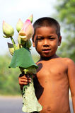 Kid in Cambodia. Poor cambodian kid selling lotus flowers Royalty Free Stock Images
