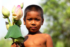 Kid in Cambodia. Poor cambodian kid selling lotus flowers Stock Photography