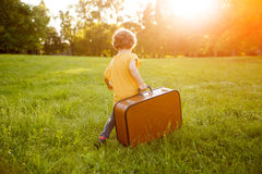 Kid carrying suitcase walking on grass Royalty Free Stock Photography