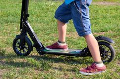Kid in casual wear on kick scooter in park.  stock photos