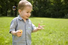 Kid Catches Soap Bubbles Royalty Free Stock Image