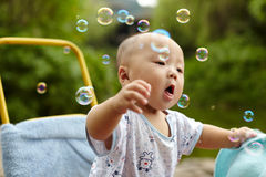 Kid catching soap bubbles Stock Images
