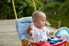Kid catching soap bubbles Stock Photo