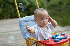 Kid catching soap bubbles Stock Image