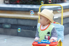 Kid catching soap bubbles Stock Photography