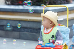 Kid catching soap bubbles Royalty Free Stock Images