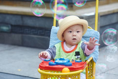 Kid catching soap bubbles Stock Photos