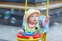 Kid catching soap bubbles Royalty Free Stock Photo