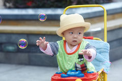 Kid catching soap bubbles Royalty Free Stock Image
