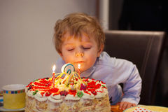 Kid celebrating birthday and blowing cake candles Royalty Free Stock Photo